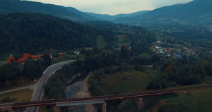 Railway bridge over the river and the mountain road. Aerial view of summer mountains in Carpathians, Ukraine stock video