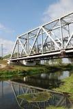 Railway bridge over small rive. White railway bridge over small river with green banks Royalty Free Stock Images