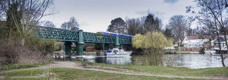 Railway bridge over Thames at Bourne End. Panorama of the river Thames  at Bourne End showing train crossing railway bridge with boat sailing under bridge Royalty Free Stock Photography