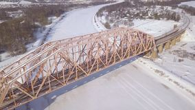 Railway bridge and railway track for train traffic over frozen river on winter landscape drone view. Suspension train. Bridge through river and car highway stock video footage