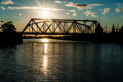 The railway bridge through the river at sunset Stock Images