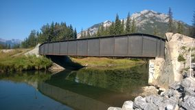 Railway bridge in Rocky Mountains. Railway bridge over calm reflecting waters in rural countryside of Rocky Mountains on sunny day with blue skies Royalty Free Stock Photography