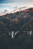 Railway Bridge and snowy Mountains Landscape. With autumn forest Travel scenery epic view Stock Image