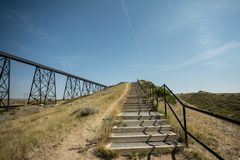 Railway bridge and stair case footpath meeting at horizon stock photography