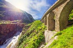 Railway bridge Teufelsbrucke over Reuss river in St. Gotthard mountain range of Swiss Alps near Andermatt Royalty Free Stock Photo
