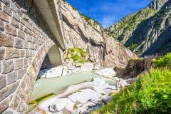 Railway bridge Teufelsbrucke over Reuss river in St. Gotthard mountain range of Swiss Alps near Andermatt Stock Photos