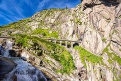 Railway bridge Teufelsbrucke over Reuss river in St. Gotthard mountain range of Swiss Alps near Andermatt Stock Image