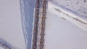 Railway bridge for train movement over frozen river on winter landscape drone view. Aerial view suspension train bridge. Through winter river stock video footage