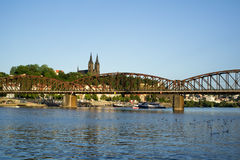 Railway bridge at Vyton under Vysehrad, Prague. Railway bridge at Vyton under Vysehrad. Vltava river, embankment with unidentifiable people, Tower and spire of Royalty Free Stock Image