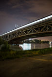 Railway bridge in Warsaw, Poland by night. Bridge by night. Train bridge with lights and dark sky, National Stadium by Vistula river. Illuminated railway bridge stock images