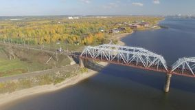 The railway bridge on which the train rides. Aerial view. The train rides on the railway bridge over the Kama river. Aerial view stock video
