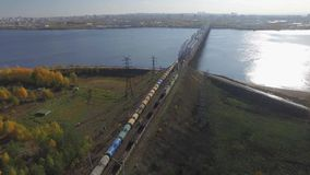 The railway bridge on which the train rides. Aerial view. The train rides on the railway bridge over the Kama river. View on the city of Perm. Aerial view stock footage
