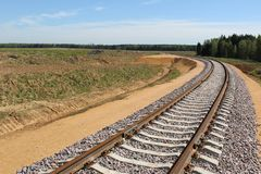 Railway track: rails, sleepers laid through fields, forests for transportation of goods and people. The railway is built of sleepers and rails.Wooden sleepers royalty free stock photos