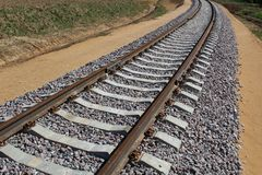 Railway track: rails, sleepers laid through fields, forests for transportation of goods and people. The railway is built of sleepers and rails.Wooden sleepers stock images
