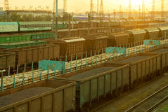 Railway cargo cars at sunset. Railway cargo cars carrying coal and logs Stock Image