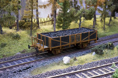 Railway carriage model with coal. On rails in landscape Stock Photos