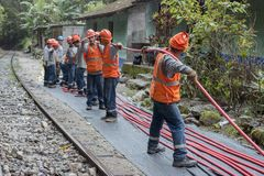 Railway construction workers. AGUAS CALIENTES, PERU- OCTOBER 26: many workers in orange uniform pull electrical cable along railway tracks in Aguas Calientes royalty free stock photography