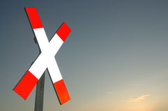 Railway cross. Red-white railway cross sign against evening sky Stock Photos