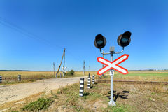 Railway crossing equipped with electric lights. Royalty Free Stock Photo