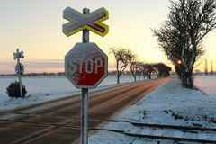 Railway crossing on a roadway with two traffic signs stop at sunrise. Colorful sky and winter landscape with many leafless trees in the Czech Republic near Stock Photos