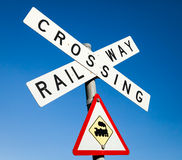 Railway crossing sign against a blue sky Stock Images