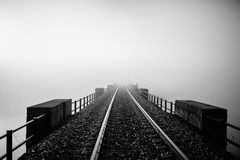 Railway disappearing into the fog. Black and white. Stock Photos