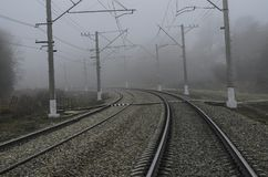 Railway for electric train. A smooth turn going into the fog. Royalty Free Stock Photo