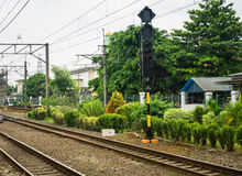 Railway with electrical cable for commuter line surrounding by trees and bushes at Depok Station photo taken in Depok Stock Photography