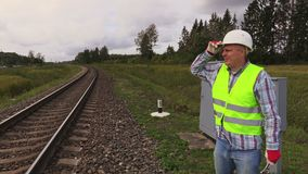 Railway electrician on rails. In autumn day stock video