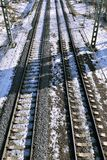 Railway embankment with rails. Railway mound with rails going into the distance, on a snowy March day Royalty Free Stock Photography