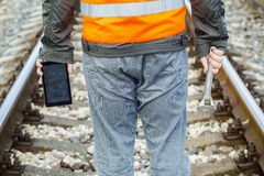Railway employee with adjustable wrench and tablet PC on railway Stock Photo