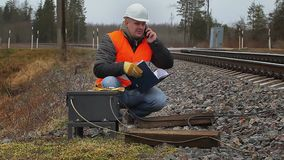Railway employee with documents talking on cell phone stock footage