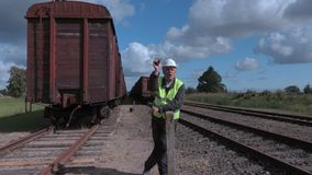 Railway employee showing stop gestures near wagons stock footage