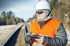 Railway employee with tablet PC near the railway Stock Photography