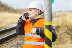 Railway employee talking on cell phone near railway Stock Images