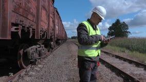 Railway employee using smart phone near wagons. In summer day stock video