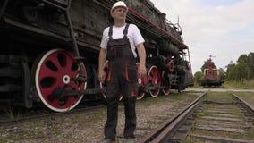 Railway employee walking near locomotive on rails stock video