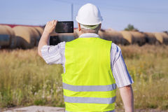 Railway Engineer filmed with tablet PC near freight wagons Royalty Free Stock Photo