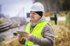 Railway engineer near rails working with tablet PC Stock Photo