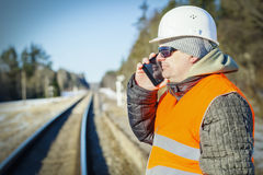 Railway engineer talking on the cell phone on railway Royalty Free Stock Photography