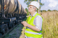 Railway Engineer using tablet PC on railway near freight wagons Royalty Free Stock Photography