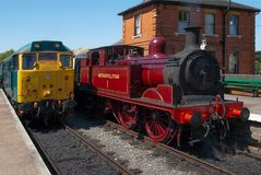 Railway Evolution. British Rail diesel Class 31 locomotive number 31438 D5557 stands alongside the panier tank 0-4-4 steam locomotive `Metropolitan 1` at North Stock Photography