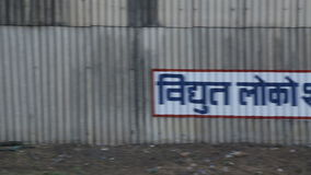 Railway fence with a sign, view during train ride in Agra. stock video