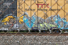 Railway freight car with graffiti. At standstill behind chain link fence Royalty Free Stock Images
