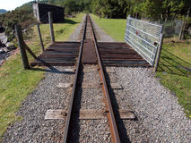 Railway with gate. A single track railway with a walkway and a gate leads into the distance Royalty Free Stock Photography