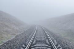 Railway go to horizon in fog Royalty Free Stock Photo