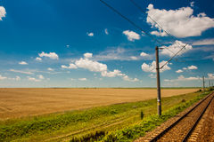 Railway goes to horizon in green and yellow landscape under blue sky with white clouds Royalty Free Stock Photo