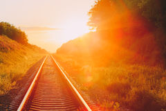 Railway Going Straight Ahead Through Summer Hilly Meadow To Sunset Stock Images