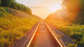 Railway Going Straight Ahead Through Summer Hilly Meadow To Sunset Stock Photos