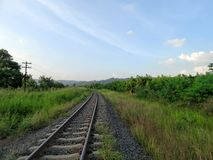Railway through green field and blue sky Royalty Free Stock Image